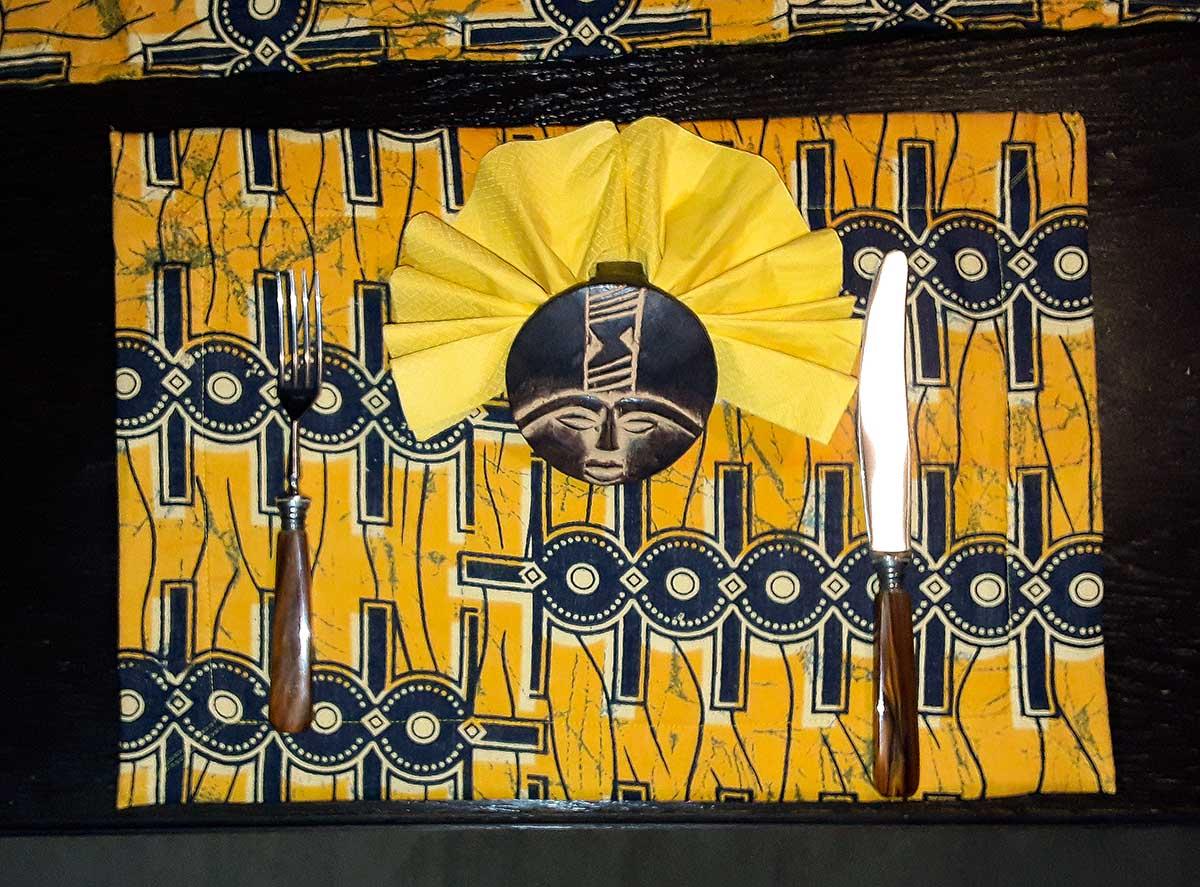 Tischset aus Kitengestoff, einfarbige Seite mit Papierserviette im Ashanti-Ring